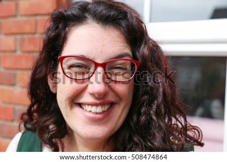 Head shot of a happy young woman with glasses wearing a green dress  with a big smile sitting in front of her house