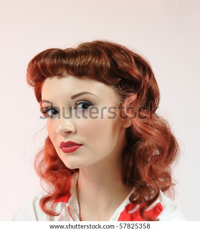 Head shot of a pretty pin-up girl on a soft pink background. - stock photo