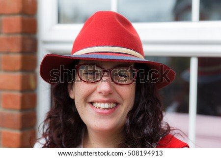 Head shot of a young woman with glasses wearing a red dress and hat with a big smile sitting in front of her house