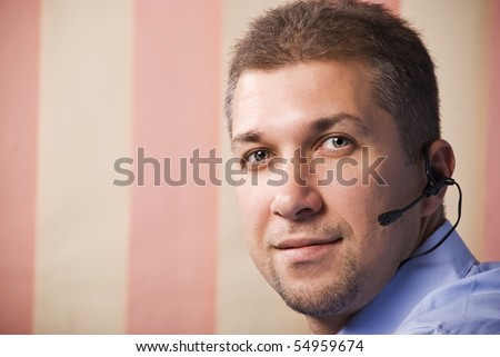 Head shot of beard man close up with headset looking you on pink vertical blinds background,copy space for text message in left part of image - stock photo
