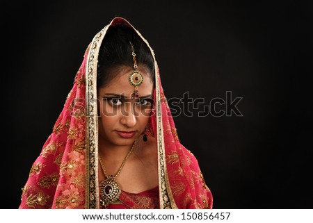 Head shot of beautiful young Indian woman in traditional sari dress, veil covering head, isolated on black background.