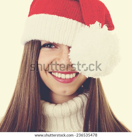Head shot of Christmas teenage girl with freckles. Closeup studio portrait of cute young woman with long brown hair and knitted Santa Claus hat. Square format, instagram filter. - stock photo