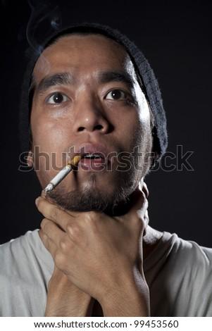 Head shot of Sick smoker having an asthma. Shot in studio with back light - stock photo