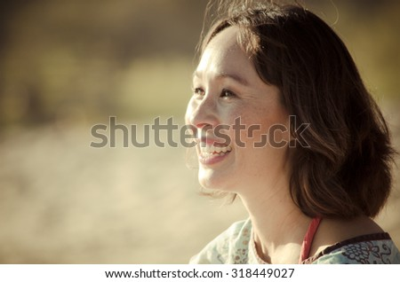 Head shot of woman sitting on the beach