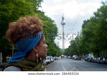 head shot of young curly woman in Berlin in front of the TV Tower