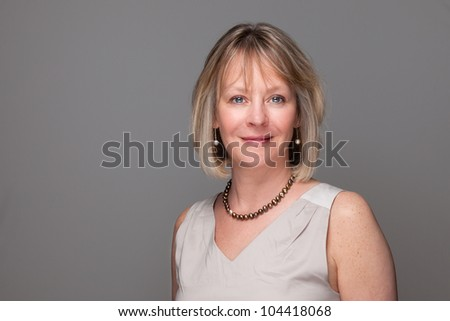 Head Shot Portrait of Attractive Smiling Elegant Woman on Grey Background - stock photo