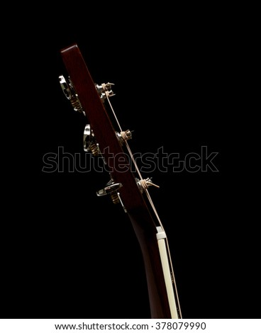 Head Stock and Neck of an Acoustic Flat top Guitar on a Black Background