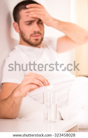 Headache. A young man drinking cure, lying in bed at home - stock photo