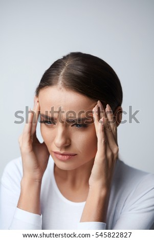 Headache And Stress. Beautiful Young Woman Feeling Strong Head Pain. Portrait Of Tired Stressed Female Suffering From Painful Migraine, Holding Hands Near Face. Health Care Concept. High Resolution