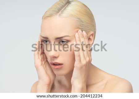 Headache concept. Young attractive blonde woman touching her head isolated on white background. - stock photo