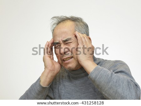 headache. Elderly man covers his face with hand