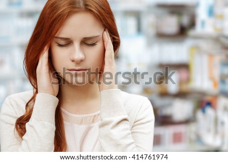 Headache. Female pharmacy client struggling with a headache rubbing her temples at the pharmacy. - stock photo