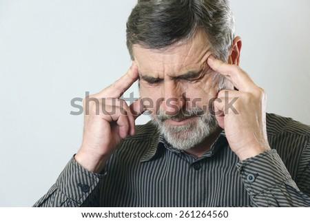 Headache, Frustrated senior man holding his head, suffering from headache - stock photo