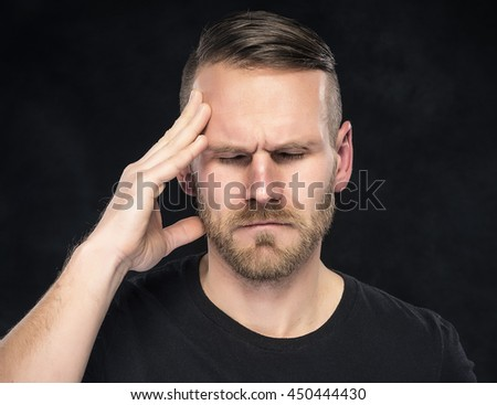 Headache in men on a dark background.