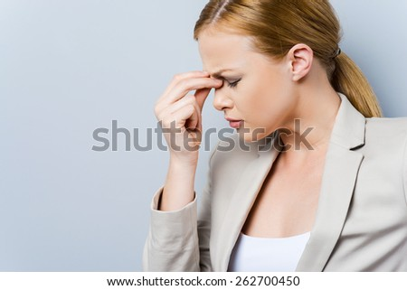 Headache is killing. Side view of depressed young businesswoman touching her face and keeping eyes closed while standing against grey background  - stock photo