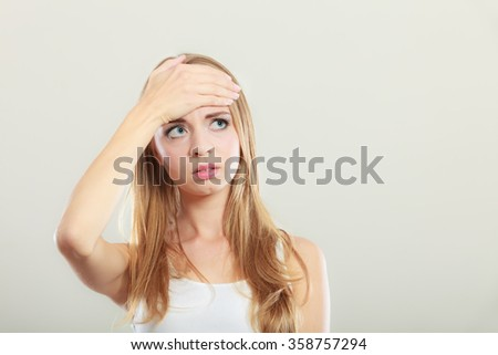 Headache, migraine and stress. Worried upset woman suffering from head pain or having high temperature. - stock photo