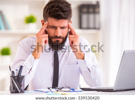 Headache. Portrait of a businessman with a beard while working in his office, holding his head