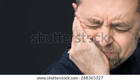 Headache. Portrait of an elderly man with face closed by hand on dark background with copy-space