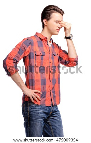 Headache. Stressed and tired young man holding hand on his hat. Isolated on white.