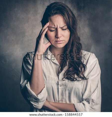 Headache - Young woman holding head