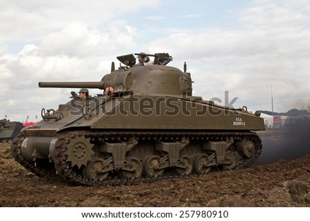 HEADCORN, UK - AUGUST 16: A restored vintage WW2 US army Sherman tank is put through its paces in the main show arena for the public to watch at the Combined Ops show on August 16, 2014 in Headcorn. - stock photo