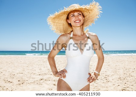 Heading to white sand blue sea paradise. Happy woman in white swimsuit and straw hat at sandy beach on a sunny day looking into the distance - stock photo
