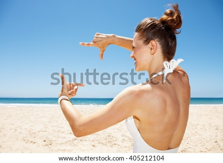 Heading to white sand blue sea paradise. Happy woman in white swimsuit at sandy beach on a sunny day framing with hands - stock photo