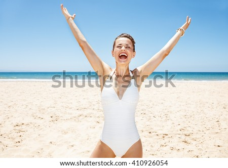 Heading to white sand blue sea paradise. Happy woman in white swimsuit at sandy beach on a sunny day rejoicing