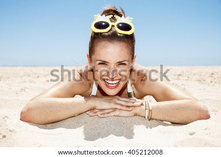 Heading to white sand blue sea paradise. Portrait of smiling woman in white swimsuit and funky pineapple glasses laying on sandy beach on a sunny day - stock photo