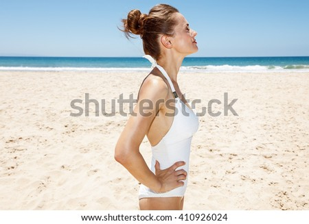 Heading to white sand blue sea paradise. Relaxed woman in white swimsuit at sandy beach on a sunny day - stock photo