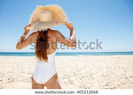 Heading to white sand blue sea paradise. Seen from behind woman in white swimsuit and straw hat at sandy beach on a sunny day - stock photo