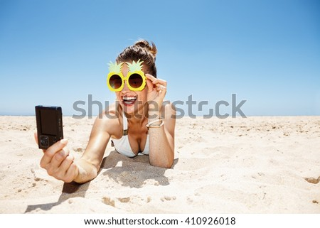 Heading to white sand blue sea paradise. Smiling woman in white swimsuit and funky pineapple glasses taking selfie at sandy beach on a sunny day - stock photo