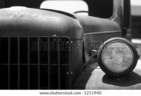 Headlight and radiator grill of old, rusty truck. Black and white photo