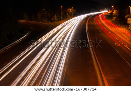 Headlight and Taillight Trails on a Busy Highway at Night - stock photo