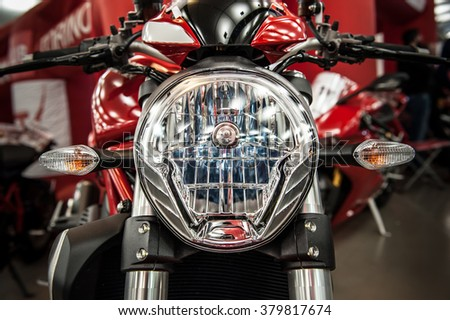 Headlight of a modern motorcycle in a salon
