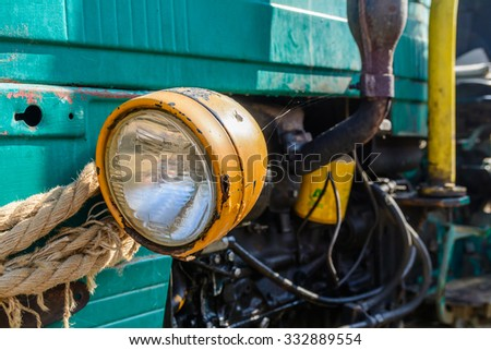 Headlight of old vehicle closeup. Colorful background of aged retro equipment in the village. - stock photo