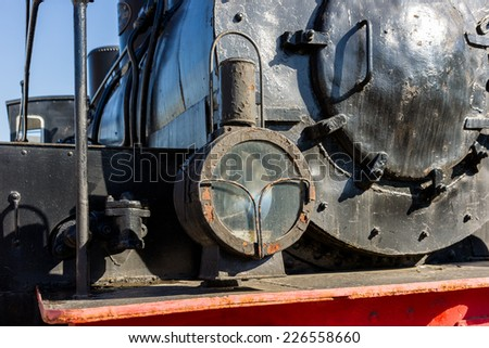 Headlight of the ancient steam locomotive. Petroleum lamp and a metal reflector inside the metal cage. Black boiler in the background. Horizontal, landscape orientation photography - stock photo