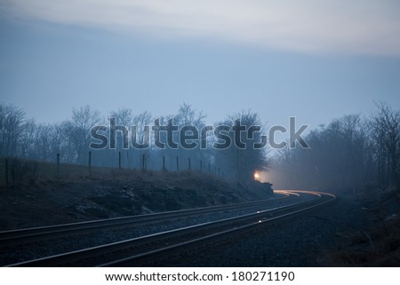 Headlight of train barely visible around a distant curve. - stock photo