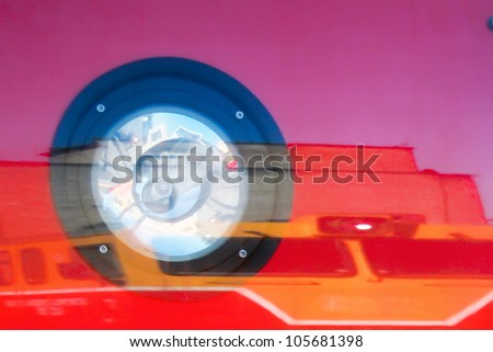 headlight reflected in the glass on the shiny surface of a train of red color with the reflections and refraction - stock photo
