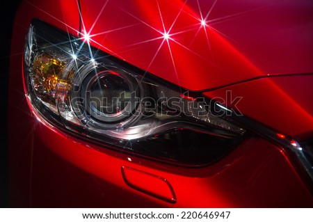 Headlights and hood of sport red car with silver stars