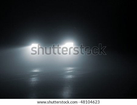 headlights of a car approaching in the dark - stock photo