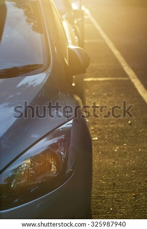 headlights of car at light sunset on the street background - stock photo