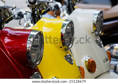 Headlights of three scooters, red, yellow and white. Shallow depth of field with the first scooter in focus. - stock photo