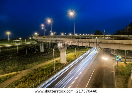 headlights racing machines.The ring road interchange in St. Petersburg at evening illumination - stock photo