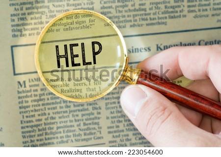 Headline of newspaper through magnifier. Headline of newspaper through magnifying glass, with Help word  - stock photo