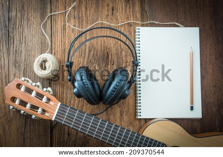 headphone guitar notebook and pencil - stock photo