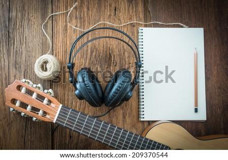 headphone guitar notebook and pencil - stock photo