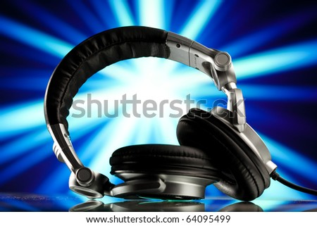 headphones against blue rays background - stock photo