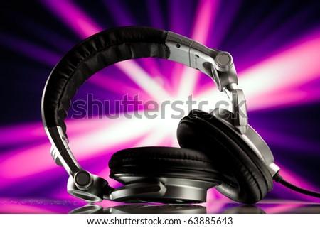 headphones against purple rays background - stock photo
