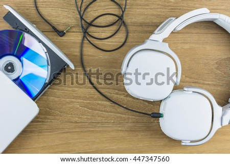 Headphones and CD-Player on wooden background./ Stereo headphone - stock photo